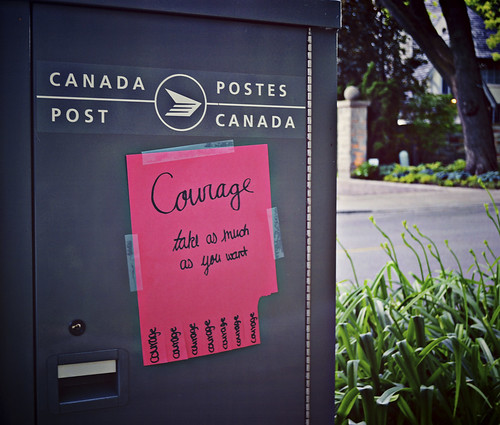 "A sign taped to a Canada Post box saying ""Courage - take as much as you need."""