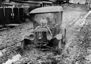 Boy sitting on the bonnet of a car bogged in mud from the 1925 flood at Innisfail, Queensland