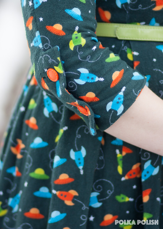 Retro space ship and flying saucer novelty print flannel dress in forest green, liume, blue, and orange with bright orange vintage buttons