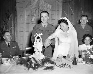 Fumiko Isumizawa and G McCaughey cutting their wedding cake, 1952