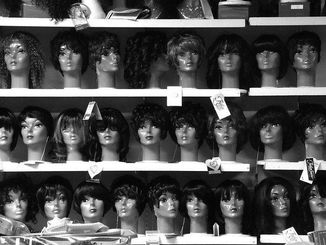 Mannequins with wigs on a store shelf