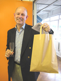 A happy shopper with a bag of goodies and a glass of bubbly