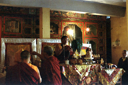 HH Sakya Trizin ringing tingsha bells, mandala offerings and initiation, on his throne with peacock feather vases, mandala, tea cup, diety torma offerings, monks, and his son, Rajpur, HP, India by Wonderlane