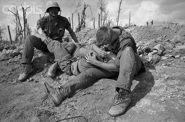 Khe Sanh, Vietnam, A wounded United States Marine is held in the arms of soldiers while awaiting medical attention during fighting of the Vietnam War on Hill 881 on May 11, 1967, by Frank Johnston