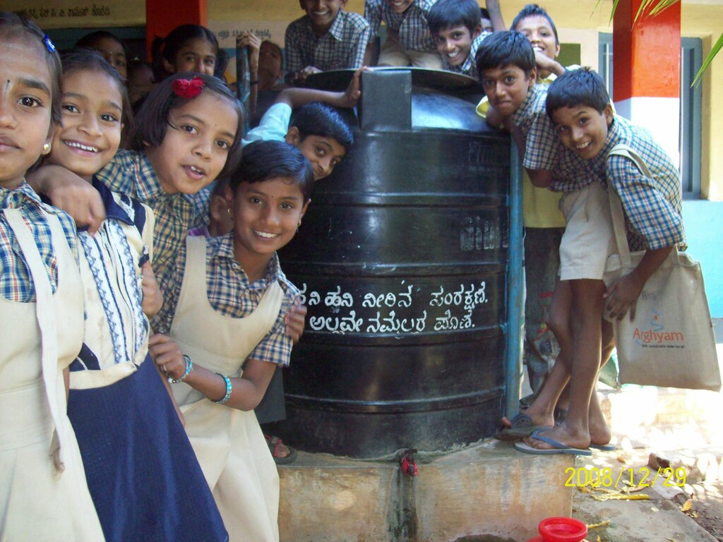 Children group around a water storage tank in their school.