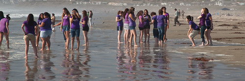 Young teen girls in purple shirts enjoy socializing on a hot day at water's edge by mikebaird