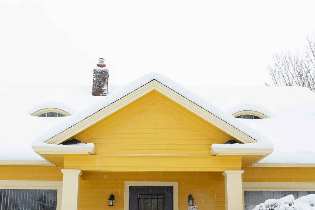 A closer view of a cheery yellow house in the snow