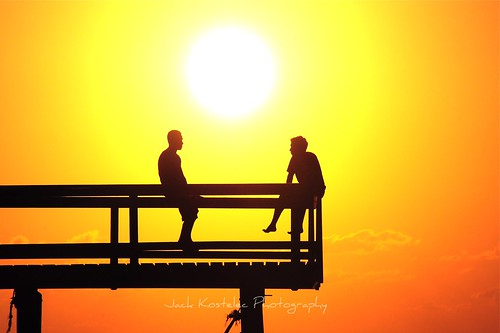 sunset orange sunlight silhouette yellow pier friendship honduras conversation roatan