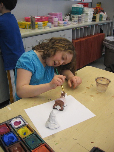Bullis student painting Buddy Bison she created from clay