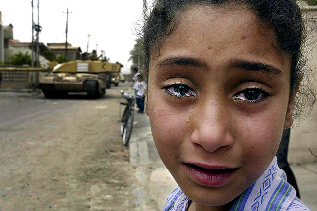 A young Iraqi girl cries as a British Challenger tank moves in on the Baath party office, by Odd Anderson