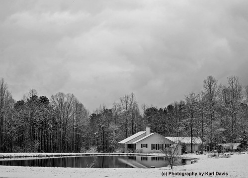 Bungalow beside pond on an overcast winter snow day