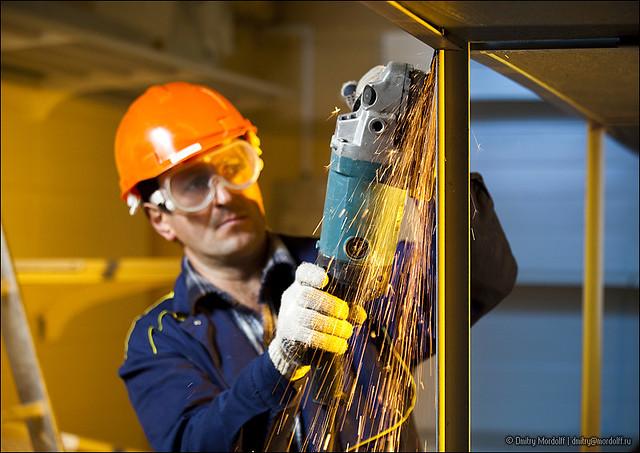 Builder grinding welds on metallic construction