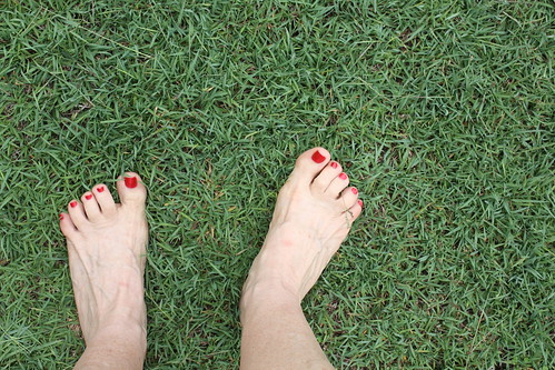 A downward facing photograph of a green yard, with two bare feet standing on the grass.