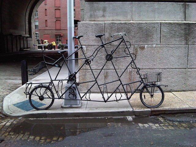 In DUMBO, a tall bicycle built for three.