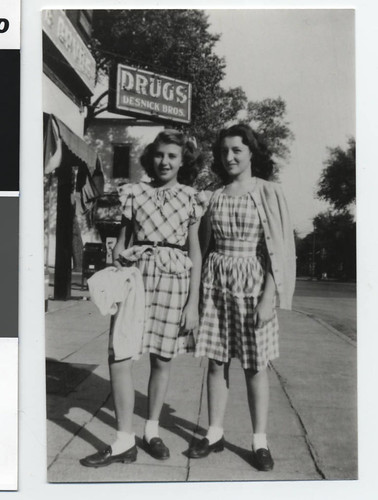 Two girls standing outside Desnick's Drug Store, Minneapolis