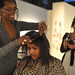 Having her hair done at the exhibiton Beauty Shop Culture