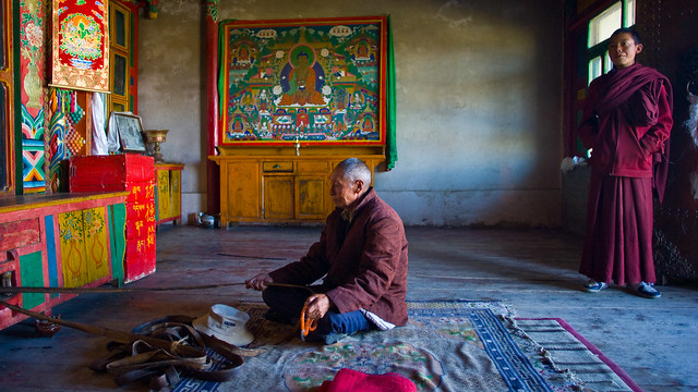 Elderly monk spins prayer wheel in Qinghai, China.