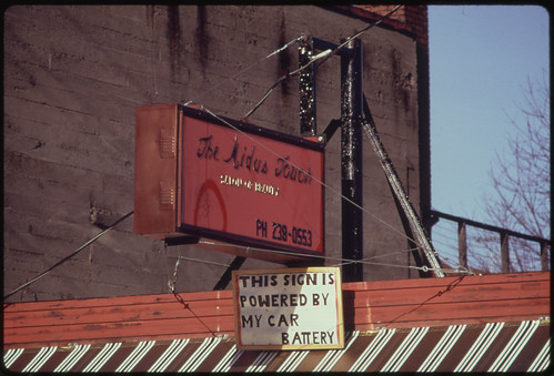 A Car Battery Operated This Neon Advertising Sign over a Business, During the Energy Crisis in December, 1973 12/1973