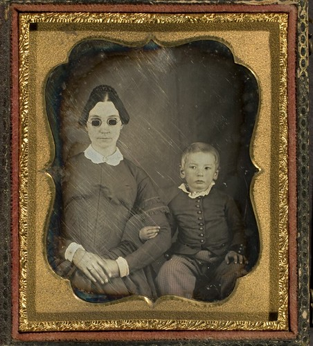 Portrait of blind woman (wearing dark glasses) and child