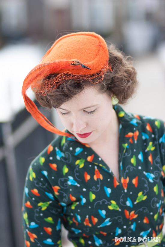 1950s orange wool hat with a veil and a faux bird of matching feathers paired with an outer-space themed novelty print dress