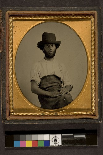 Portrait of man in hat wearing leather apron
