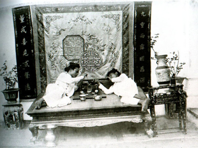 Two Vietnamese in a private smoking room furnished with an opium bed
