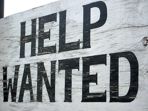 Giant wooden help wanted sign.