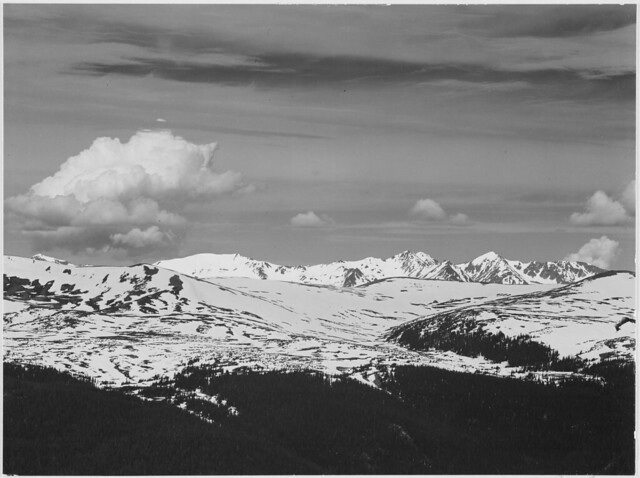 """View at timberline, dark foreground, light snow capped mountain, gray sky, """"Rocky Mountain National Park. Never Summer Range,""""Colorado."""