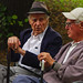 Two retirees speak on a park bench