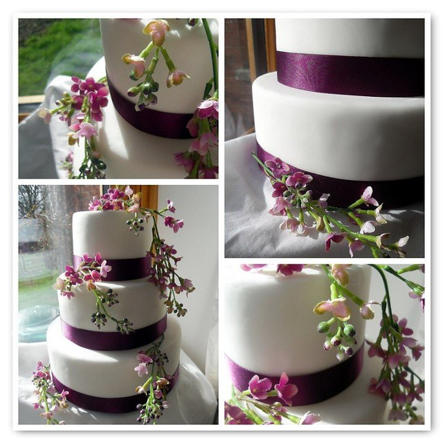 Plain white fondant covered 3 tier cake with deep purple satin ribbons