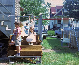 That's me with the plaid shirt and sis in a pink dress looking pouty for some reason at a birthday party.  Some cool cars in the background!  Milford, Connecticut. Aug 1967