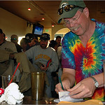 Larry McCourt (right) writes a check for the Pioneer Hockey ticket auction while others battle for free shirts at the 2005 Ice Bowl at West Arvada Disc Golf Course.