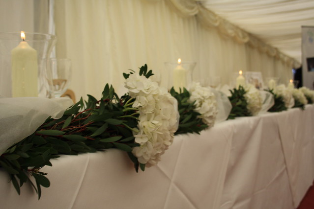 Top table garland using hydrangeas and hurricane vases for marquee wedding