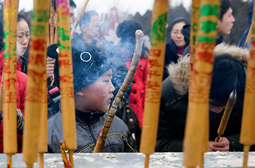 Boy prays with incense during a temple fair at  the Temple of Earth in Beijing on the first day of the Chinese Lunar New Year of Tiger.