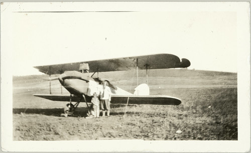 Woman in  jodhpurs with kid by a very early light plane