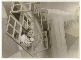 Woman leans out of window of ice-covered Kosciuszko chalet, c. 1930s, by Sam Hood