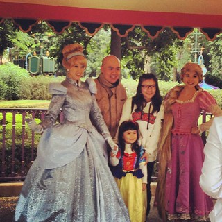 A family poses with Cinderella and Rapunzel. The little girl is dressed up as Snow White.