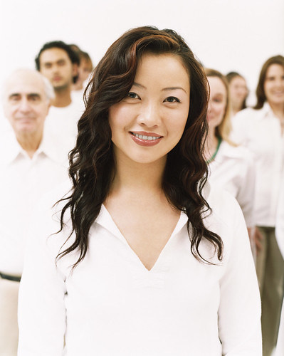 Portrait of a Smiling Young Woman in a White Top Standing in Front of a Crowd