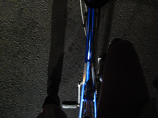Red light, blue bike, black night.
