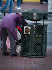 Homeless woman rummaging through a trash can