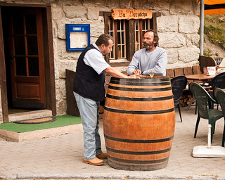 YES TWO DUDES DRINKING WINE ON TOP OF A GIANT BARREL