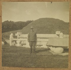 [Western man in uniform posing in front of burial mound]