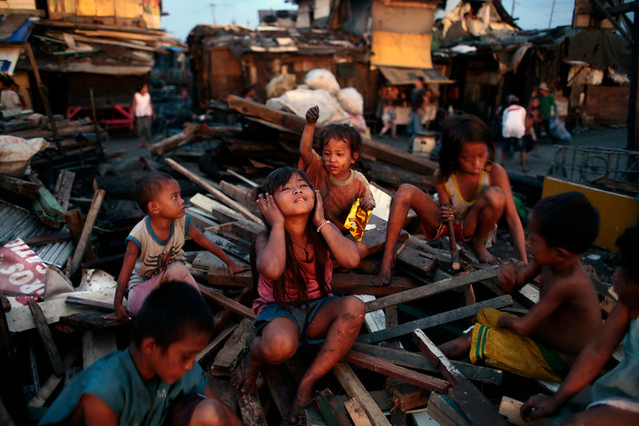 A young girl listens to imaginary headphones as children pry nails from old wood to earn money for school. Bitas Tambakan, also known as Smokey Mountain. Tondo District Manila