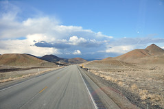 asphalt, horizon, highway, cloud, mountain, sand, valley, road, aeolian landform, hill, natural environment, desert, landscape, badlands, sky, infrastructure, mountainous landforms,