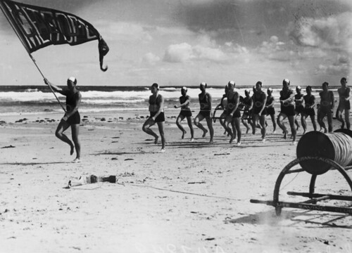 Metropolitan-Caloundra Surf Lifesavers marching in a parade on the beach at Caloundra, 1938