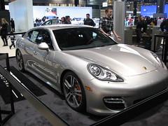convertible(0.0), automobile(1.0), automotive exterior(1.0), wheel(1.0), vehicle(1.0), performance car(1.0), automotive design(1.0), porsche(1.0), porsche panamera(1.0), auto show(1.0), bumper(1.0), land vehicle(1.0), luxury vehicle(1.0), sports car(1.0),