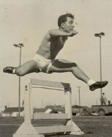 1940s shirtless man athlete track shorts jumping hurdles