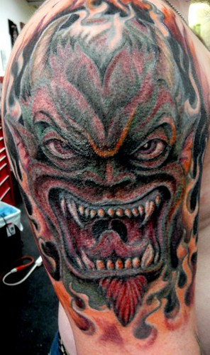 Flames Tattoo Howling Demon With Around It Located On Upper Arm