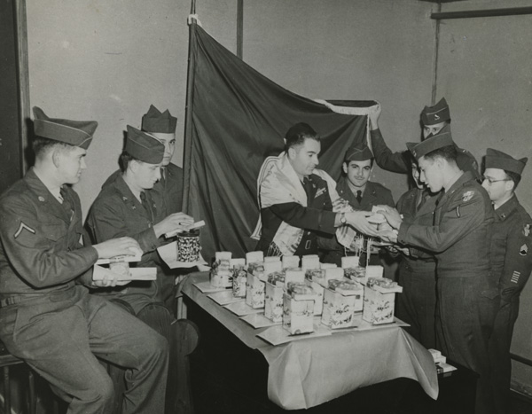 Chaplain Dicker hands out Hanukah gifts to soldiers in Austria, 1951