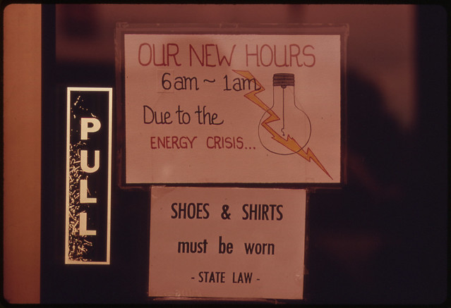 Sign Posted in a Doorway Entrance to a Restaurant Explaining Shorter Hours Due to the Fall of 1973 Energy Crisis in Oregon. The Business Was Located Along Interstate #5 10/1973